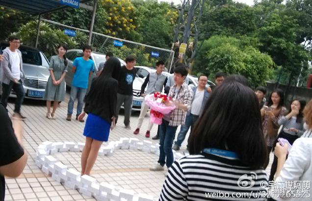 Chinese macht seiner Freundin einen Heiratsantrag in einem Herzen aus 99 iPhones, umgeben von Freunden