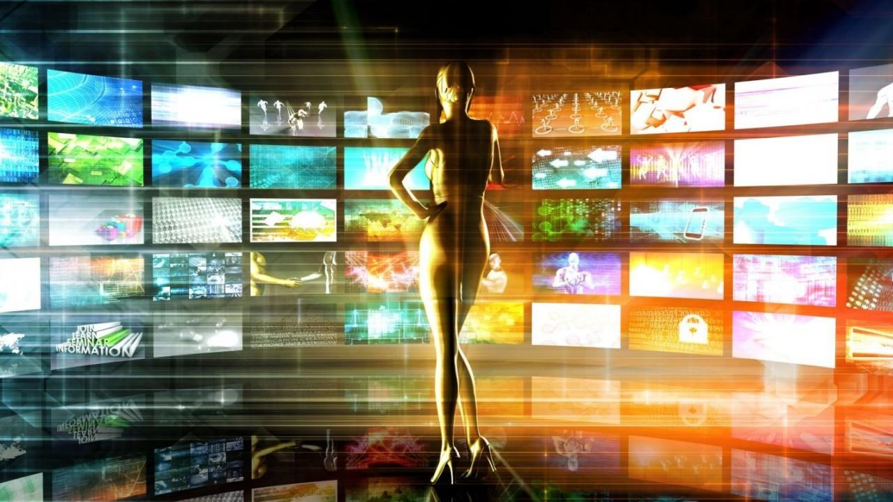 Frau steht vor grosser Wand aus Fernsehern